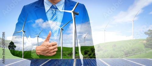 Photo Double exposure graphic of business people working over wind turbine farm and green renewable energy worker interface