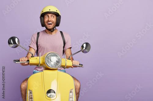 Fotografía Happy male biker or courier drives yellow scooter, wears protective helmet, casu