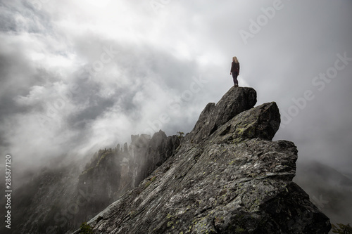 Adventurous Girl on top of a rugged rocky mountain during a cloudy summer morning. Taken on Crown Mountain, North Vancouver, BC, Canada.