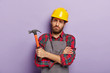 canvas print picture - Gloomy unhappy male repairer has sad tired look, keeps hands crossed, holds hammer in hand, fatigue after repairing and manual work, wears special uniform. Handcrafting, hammering, building.