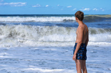 Large And Foamy Waves Rushed To The Shore, Where The Teenager Stands And Looks Into The Sea Distance