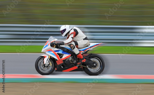 Fotografia Motorcycle rider racing at high speed on race track