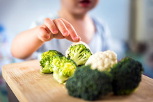 Baby Boy Hands Touch And Take Raw Fresh Broccoli And Cauliflower From Wooden Board Indoor. Baby Exploring Vegetables