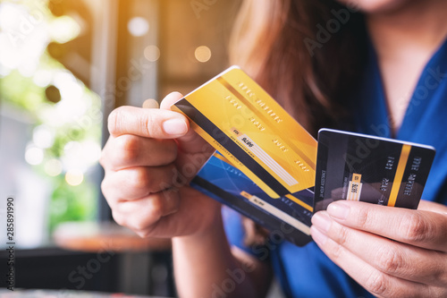 Closeup image of a woman holding and choosing credit card to use Fototapeta