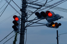 Silhouette Of Four Traffic Lights Hanging From The Same Post And Electricity Cables At Dusk In Japan.
