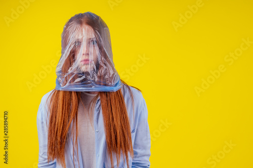 Photo redhaired ginger european woman suffocation head in blue polyethylene package in studio yellow background