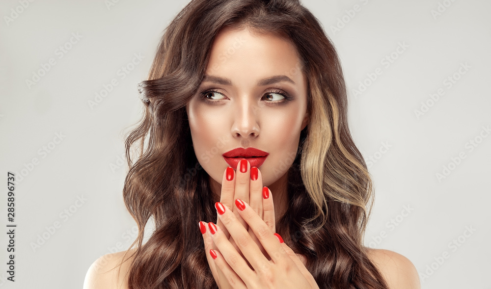 Fototapeta Beautiful girl  long , curly hair . Model woman showing a red   manicure on nails   . Cosmetics and makeup
