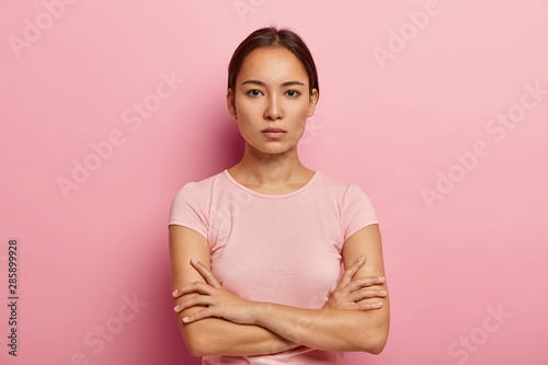 Fotografiet  Headshot of serious korean woman looks with calm face expression, keeps arms folded, has healthy fresh skin, wears rosy t shirt, stands indoor