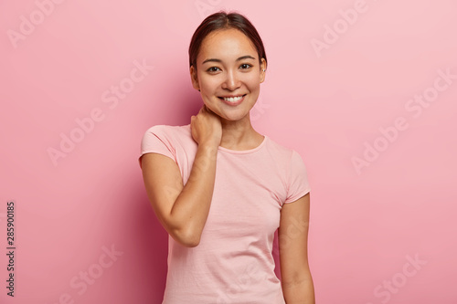 Fototapeta Portrait of feminine girl with pleasant smile, gentle look, touches neck, has delighted face expression, has pleasant talk with close friend, dressed in casual outfit, isolated on pink background obraz