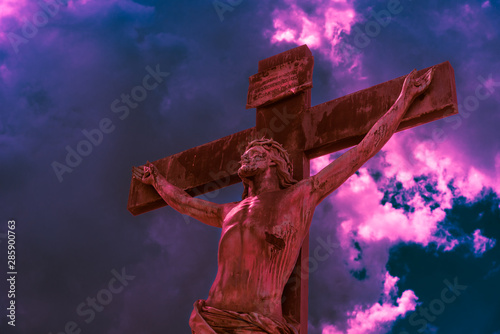 Fotografía Crucifix lit by red bloody light against a dramatic sky with purple hues