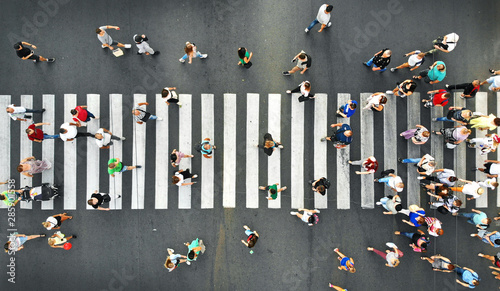 Aerial. People crowd motion on pedestrian crosswalk. Top view from drone.