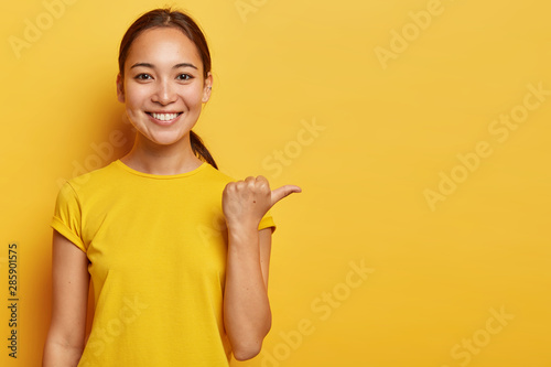 Fototapeta Studio portrait of young cheerful Asian female points away with thumb, happy face expression, demonstrates copy space for advertisement, has pleasant appearance, wears bright yellow clothes. obraz