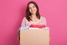 Horizontal Shot Of Happy Female Posing Isolated Over Pink Background, Holding Carton Box With Rausable Clothes, Clothing For Poor People, Charming Woman Making Charity, Dressed Striped Shirt.