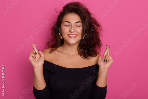 Close up portrait hopeful beautiful woman, attractive lady crossing her fingers with closed eyes, hopes and asking best, wearing black shirt with bared shoulders, posing isolated over pink background. - 285902543