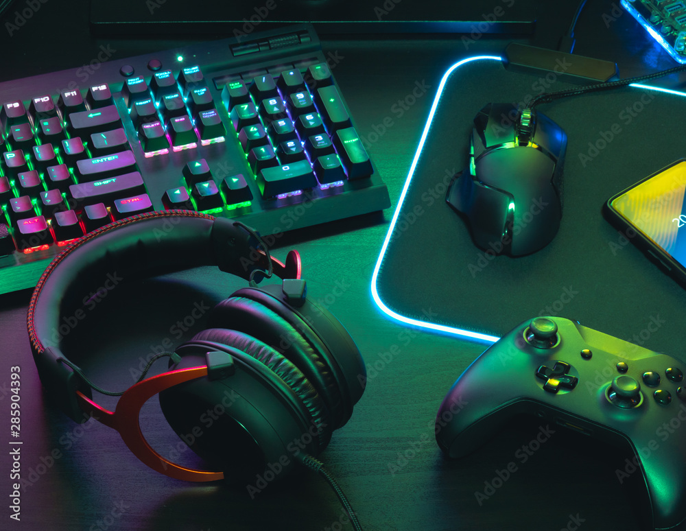 Fototapeta gamer work space concept, top view a gaming gear, mouse, keyboard, joystick, headset, mobile joystick, in ear headphone and mouse pad on black table background.