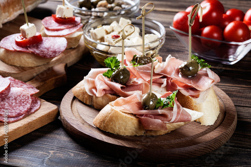 Photo Spanish tapas with slices jamon serrano, salami, olives and cheese cubes on a wo