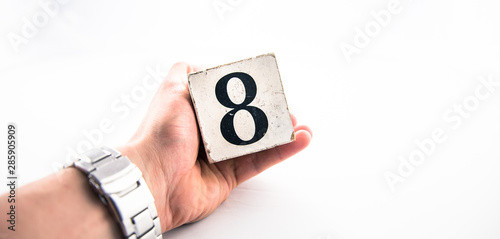 A hand holding digit number 8 (eight) on white background Canvas-taulu