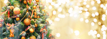 Christmas Tree Decorated With Golden Balls And Toy Bears On A Blurred, Sparkling And Fabulous Fairy Gold Background With Beautiful Bokeh, Copy Space, Banner Format.