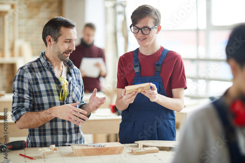 Photo Waist up portrait of mature carpenter talking to smiling young apprentice in wor