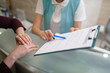 Receptionist of dentistry showing the form to fill in and sign