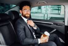 Handsome Bearded Manager Sitting With Coffee To Go On The Backseat Of The New Car.