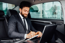 Handsome, Bearded, Smiling Businessman Working On The Backseat Of The Car And Makes Notes In The Notebook From His Laptop.