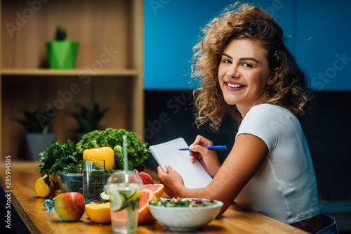 Obraz Nutritionist working in office. Doctor writing diet plan on table and using vegetables. Sport trainer. Lifestyle. - fototapety do salonu
