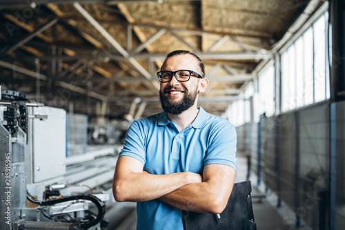 Young engeneer manager with beard checking manufactory, workplace and machinery in big factory.