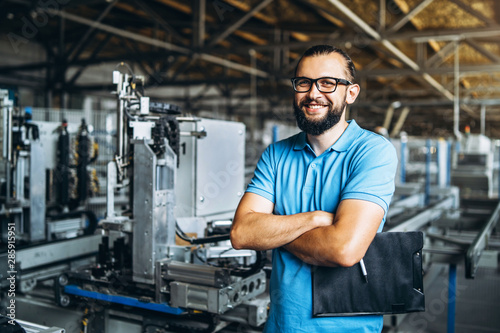 Fotomural  Young engeneer manager with beard checking manufactory, workplace and machinery in big factory