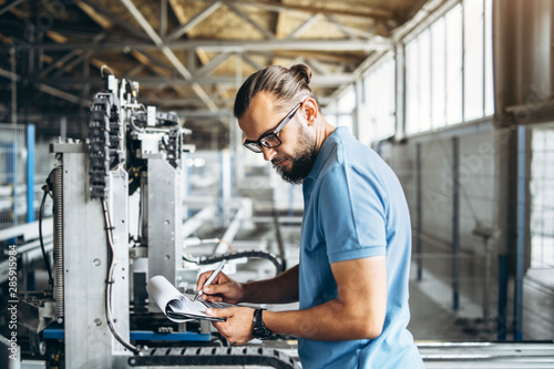 Stampa su Tela  Young engeneer manager with beard checking manufactory, workplace and machinery on big factory