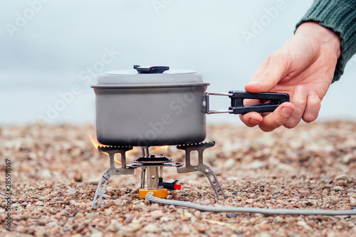 Fotografija The pan with the porridge stands on the gas burner (Camping Stove)