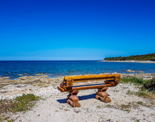 A Wooden Bench Located Directly On The Beach, With The View On Calm, Shallow Sea Water. There Are Barely Any Waves On The Surface. The Water Is Very Clear. Few Bigger Stones Protrude From Water.