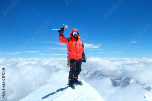 Fototapeta Happy man climber in bright red down jacket reaches the summit of mount Everest, Nepal. obraz