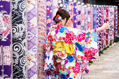 Obraz na plátně Kimono women takes picture with Kimono Forest Different kimono fabrics in transp