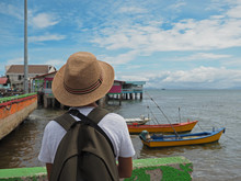 Rear View Of A Young Asian Traveller Looking Out Toward The Ocean And Blue Sky.