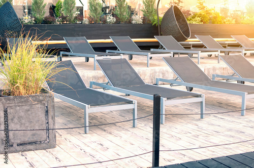 Fotografija Black chaise lounges near the swimming pool in tropical resort