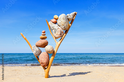 Carta da parati  Multicolored balanced stones on an wooden snags, on a blue sky and sea backgroun