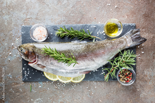 Cuadros en Lienzo Raw trout fish on slate with rosemary and lemon on a stone table, top view