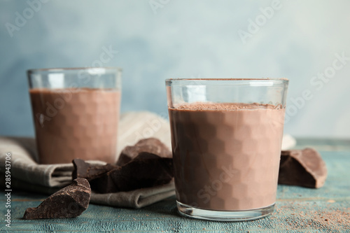 Fototapeta Glasses with tasty chocolate milk on wooden table. Dairy drink obraz