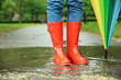 Leinwanddruck Bild Woman with umbrella and rubber boots in puddle, closeup. Rainy weather