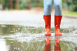 Leinwanddruck Bild Woman with red rubber boots jumping in puddle, closeup. Rainy weather