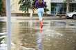 Leinwanddruck Bild Woman with red rubber boots running in puddle, closeup. Rainy weather