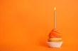 canvas print picture - Birthday cupcake with candle on orange background, space for text