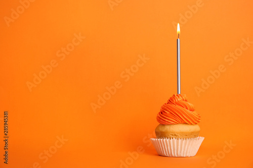 Photo  Birthday cupcake with candle on orange background, space for text