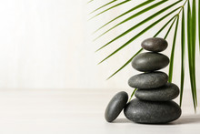 Stack Of Spa Stones And Palm Leaf On Table Against White Background, Space For Text