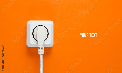 Fotomural  White cable plugged into power outlet on orange wall background with copy space