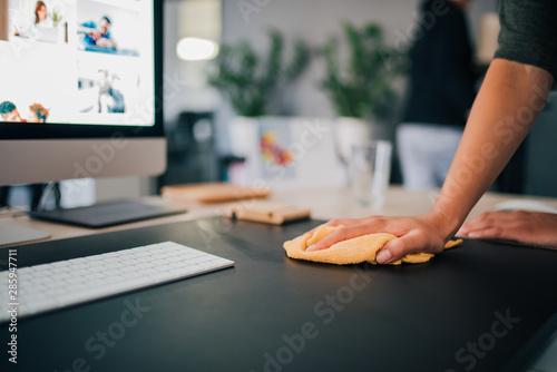 Fototapeta Hand of a woman wiping work desk, close-up. obraz