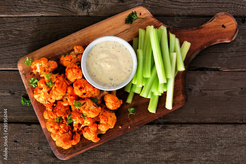 In de dag Buffel Cauliflower buffalo wings with celery and ranch dip. Top view on a wood paddle board. Healthy eating, plant based meat substitute concept.