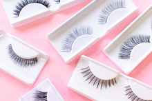 Various False Eyelashes On A Trendy Pastel Pink Background. Beauty Pattern. Cosmetic Products For Makeup Artist. Closeup.