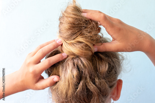 Fototapeta The girl straightens the disheveled bun on her head with her hands. Modern fast hairstyle. Blue background. Blond curly hair. obraz